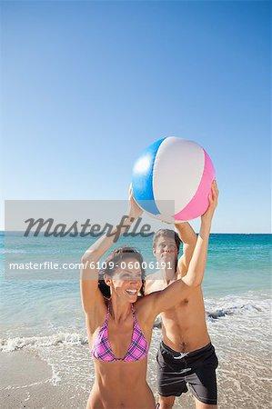 Femme jouant avec son petit ami sur la plage en face de la mer