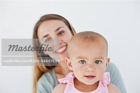 Kind in die Kamera schaut, während vor einem grauen Hintergrund