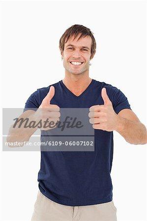 Homme souriant avec ses pouces vers le haut en accord tout debout