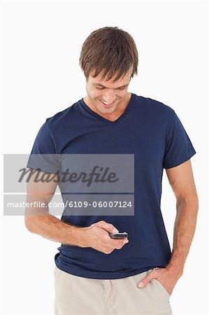 Détendue jeune homme envoie un texte tout en debout avec sa main dans sa poche