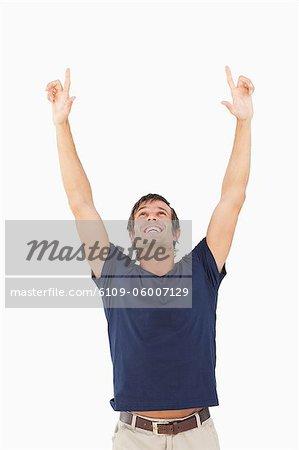 Homme souriant, levant les bras au-dessus de sa tête contre un fond blanc