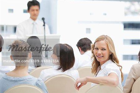 Als sie sieht hinter ihr während einer Präsentation lächelnde Frau