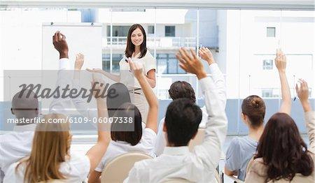 Public regarder une femme d'affaires qu'elles soulèvent leurs bras au-dessus de leur tête