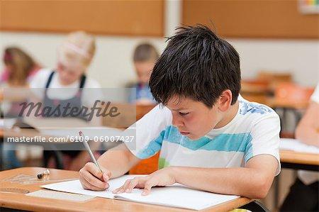 Étudiant primaire axée sur son cahier d'exercices