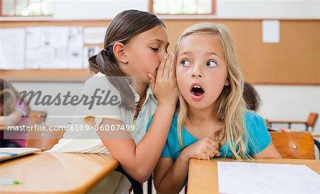 Little Schoolgirl erzählen ihre Schulkameradin ein Geheimnis