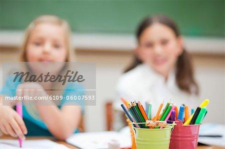 Porte-crayons sur table de peinture aux élèves du primaire