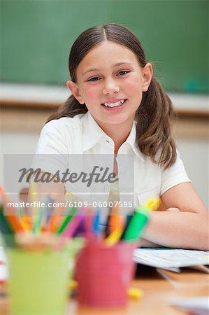 Sourire des élèves du primaire à côté de la porte crayons