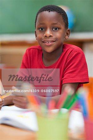 Élèves du primaire souriant assis au bureau au cours de la classe