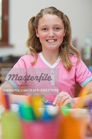 Sourire de petite fille assise au bureau au cours de la classe d'art