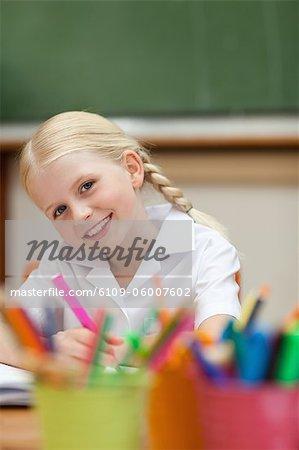 Heureuse petite fille souriante souffrir en classe