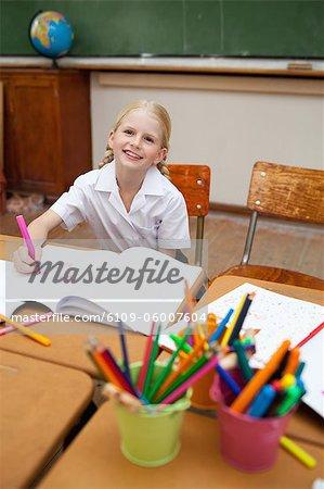 Sourire de petite fille assise au comptoir à côté de la porte-plumes