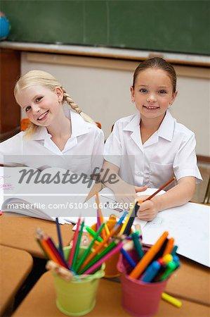 Fillettes souriantes peinture au cours de la classe