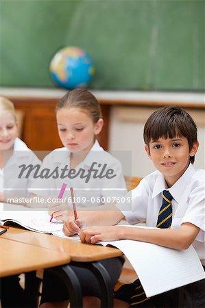 Petit garçon assis à côté de camarades de classe
