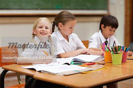 Sourire de petite fille assise à côté de camarades de classe