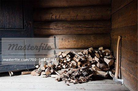 Tas de bois de chauffage et d'une hache au coin de la cabane en rondins