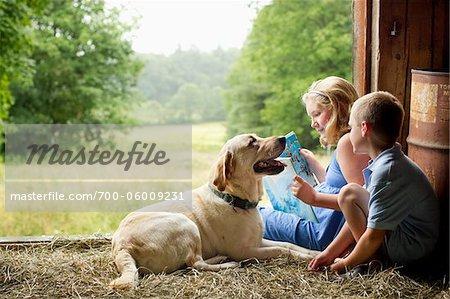 Kinder lesen in der Scheune mit Hund