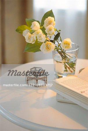 Roses blanches en verre avec un livre ouvert sur la Table