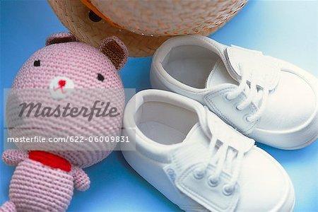 Chaussures de bébé, jouets et un chapeau sur chaise