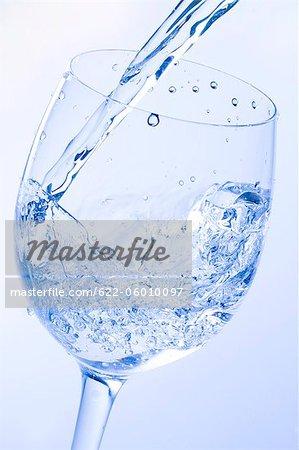 L'eau coulée en verre avec fond coloré