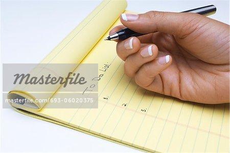 Frau schreiben Liste mit Aufgaben zu tun, Nahaufnahme der hand