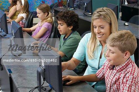 School children using computers with teacher in classroom