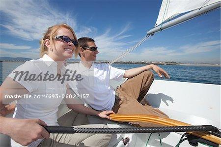 Jeune couple se détendre sur le pont du bateau à voile