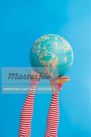 Pieds en chaussettes rayées avec chaussures colorées, tenant le globe