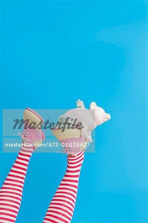 Pieds en chaussettes rayées avec chaussures colorés holding tirelire