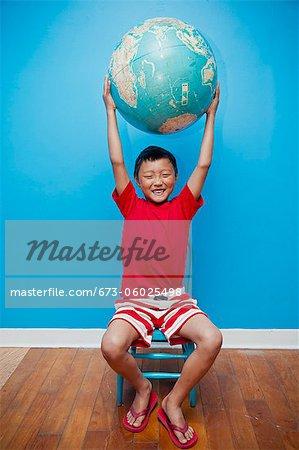 Garçon assis tenant le globe