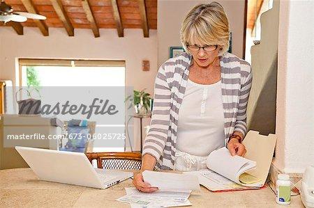 Frau Büro mit Computer und Rechnungen zu Hause arbeiten