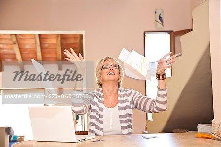 Frau am home-Office-Rechnungen in die Luft werfen