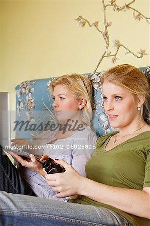 Zwei junge Frauen, die Video-Spiel im Schlafzimmer
