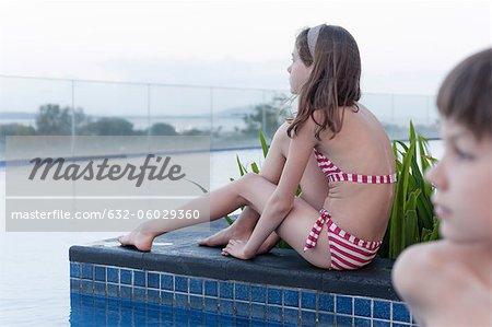 Girl in bikini sitting by poolside