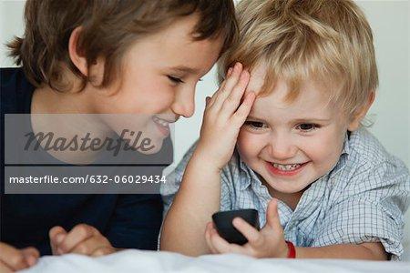 Frères jouant avec téléphone portable