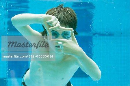 Garçon nage sous l'eau dans la piscine, mains jointes en forme de cadre du doigt