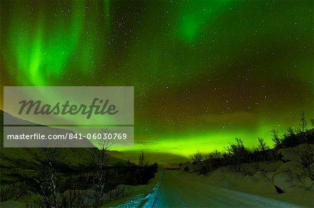 Aurora borealis (Northern Lights) vu sur une neige couverte road, Troms, Nord Norvège, Scandinavie, Europe