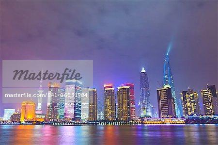 Pudong-Skyline bei Nacht durch den Fluss Huangpu, Shanghai, China, Asien