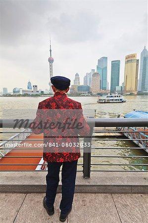 Ein Mann, der Blick auf die Skyline von Pudong aus der Bund durch den Fluss Huangpu, Shanghai, China, Asien