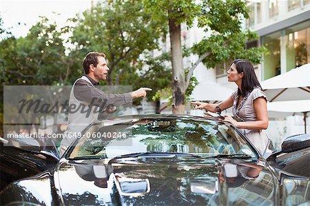 Couple en faisant valoir plus de voitures de sport