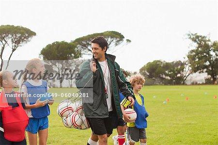 Trainer tragen Fußbälle auf Stellplatz