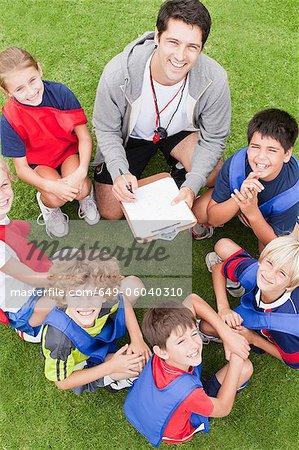 Trainer im Gespräch mit Kinder-Fußball-team