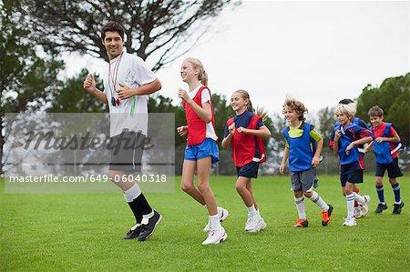Coach training children on field