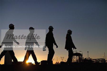 Silhouette des travailleurs à la raffinerie de pétrole