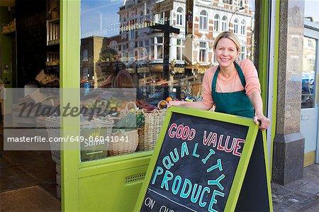 Épicier sourire permanent à l'extérieur du magasin
