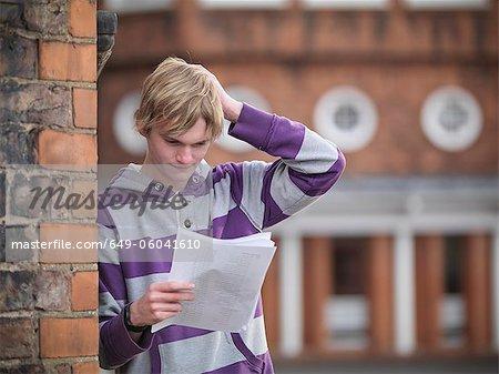 Upset student reading grades at school