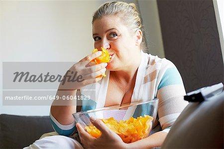 Femme souriante, manger des chips sur canapé