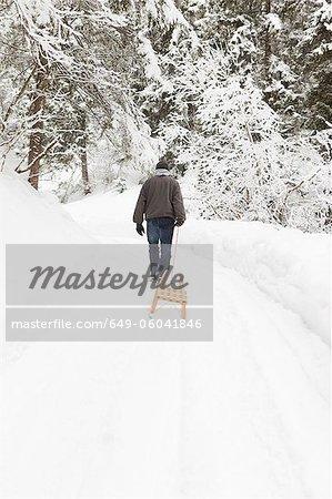Homme tirant des traîneaux en champ neigeux