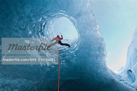 Escalade hors de la grotte de glace grimpeur