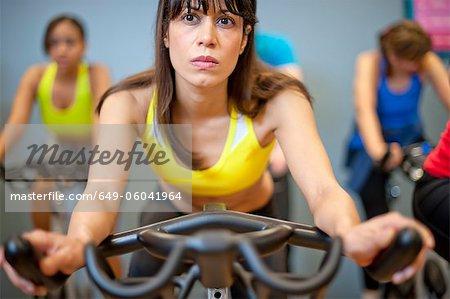 Personnes qui utilisent des machines de spin dans la salle de gym
