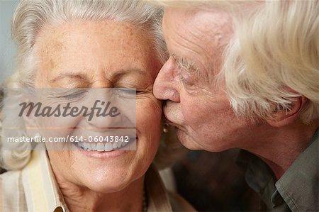 Senior man kissing senior woman on cheek